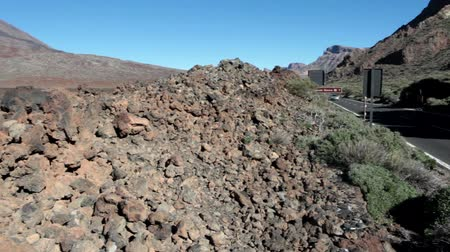 hardened lava : TENERIFE, SPAIN - CIRCA JAN, 2016: A lot of hardened lava pebble are on curbs of route TF-21. National park Teno is in central part of Tenerife. Route TF-21 is passing near the Teleferico car station