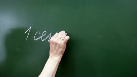 мел : Caucasian senior teachers hand writing with chalk on a green blackboard the phrase September 1 in Russian, close-up view