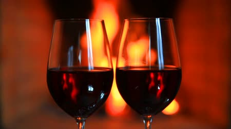 log cabin : Two glasses of red wine near a fireplace