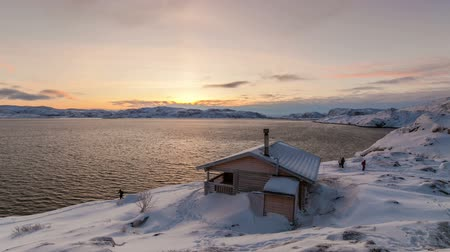 домик : Cottage on the shore of the Arctic Ocean at dawn in winter
