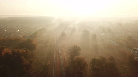 Railway track at sunrise in the fog. View from the drone