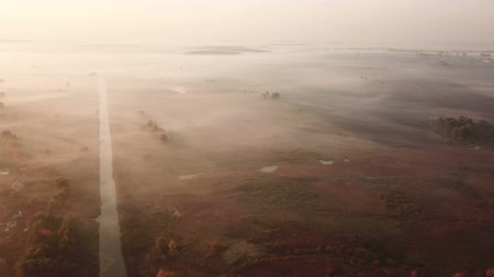 River in the morning fog, in the rays of the dawn sun. Drone footage.