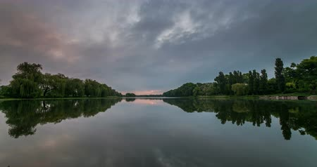Timelapse of beautiful cloudy sunrise in a lake with reflection.