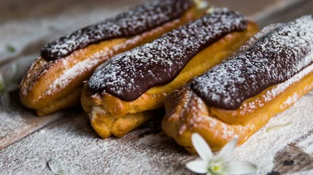 baked pudding : Traditional French dessert. Eclair with chocolate icing in powdered sugar