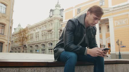 rekonstrukce : Young brutal man uses a smartphone while sitting in a beautiful European city. Slo-mo Dostupné videozáznamy