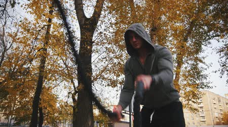 wrestler : Young athlete in Hoodie trains with battle ropes in the autumn park Stock Footage