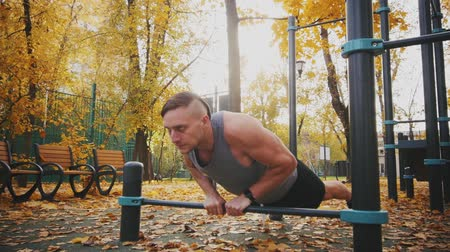 technics : Young athlete does push up exercise with narrow chest grip in autumn park