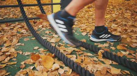 wrestler : Young athlete coming to battle ropes in yellow leaves in a park Stock Footage