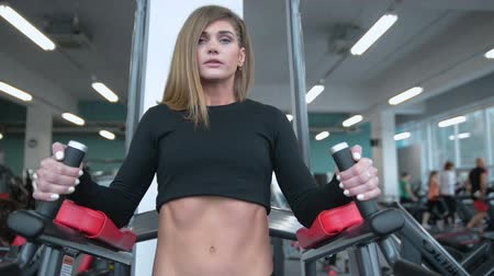 kulturystyka : Beautiful sexy athletic young Caucasian girl working out training arms abs legs butt, ass in the gym gaining weight pumping up muscles bicep with dumbbells and on machines gaining weight and poses Wideo