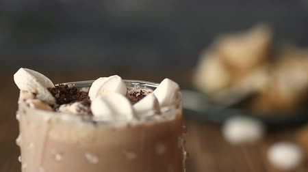milk shake : delicious cocoa drink coffee or hot chocolate, cold beverages with a plate of desserts and chocolate chips and mug full of marshmallow in glass on the wood table closeup food and drink sweet concept