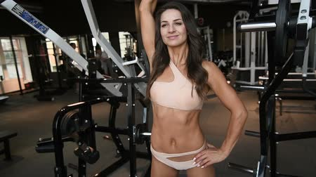 pretty caucasian fitness woman pumping up muscles workout fitness and bodybuilding concept gym background abs exercises in gym naked torso Stock Footage