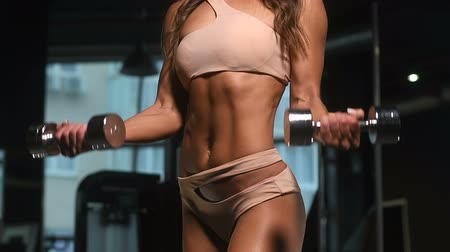 pretty caucasian fitness woman pumping up muscles workout fitness and bodybuilding concept gym background abs exercises in gym naked torso Vídeos