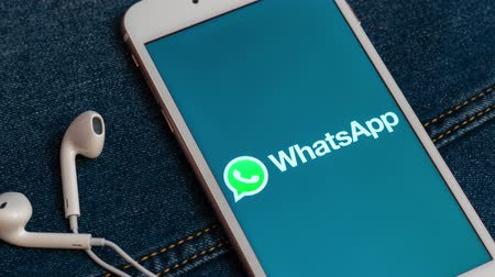 dividir : Tallinn  Estonia - May 19, 2019: White iPhone with logo of social media WhatsApp on the screen. Denim jeans background. Good for marketing and business concept or illustrative for news media,