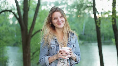 hipster : Young shy girl with long hair holds a cup of tea or coffee in hands against the blurred nature background. Pretty woman in jeans jacket smiles and drinks beverage. Stock Footage