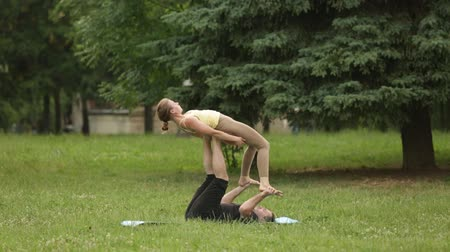 posição : Beautiful couple practicing acro yoga. Young yoga instructors practice in a city park on green grass. Two successful young people perform acro yoga exercises. Man and a woman learn yoga at sunset.