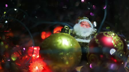 ded : Miniature Santa Claus figure between two toy Hanging Baubles for a Christmas tree. Silver Santa on a wooden surface surrounded by flashing lights.