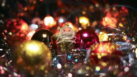 ornamentação : Miniature Santa Claus figure between four toy Hanging Baubles for a Christmas tree. Golden Santa on a wooden surface surrounded by flashing lights.