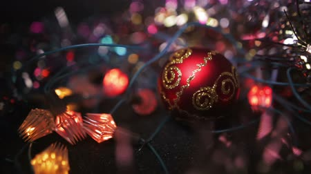 Рождественский бал : Christmas and New Year Decoration. Hanging Bauble close up. Abstract Blurred Bokeh Holiday Background. A red toy ball for a Xmas tree lies on a wooden surface surrounded by garlands. Стоковые видеозаписи