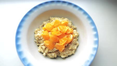 изюм : Closeup shot of healthy breakfast, oatmeal porridge with milk and mandarins. Oat flakes filled with milk in a faience dish on a white background. Organic food concept for good health.