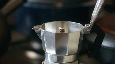 Italian coffee is ready in the moka cofeepot. A mans hand takes a coffee maker from a cooker