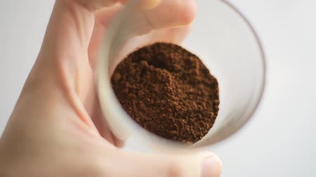 Professional barista shows freshly ground high quality coffee and the degree of its roasting. A mans hand rotates a glass beaker with ground coffee.