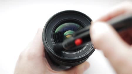 professional photography : The photographer or videographer cleans front lens from dust and dirt with the help of a professional cleaning brush.