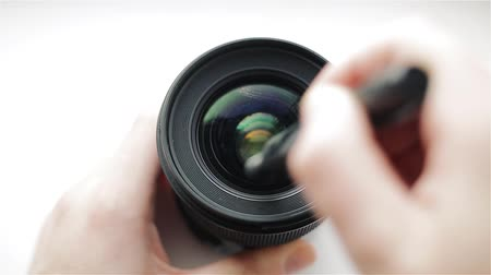 A professional photographer or video cameraman cleans the front glass of the photographic lens with a pen or a brush cleaner. Professional cleaning system for optics.