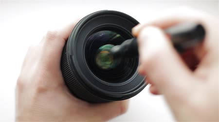 An experienced photographer or video operator intensively cleans the front glass of the photographic lens from dirt and fingerprints with a professional cleaning handle for optics.