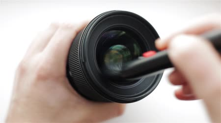 The photographer or videographer cleans front lens from dust and dirt at an angle with the help of a professional cleaning brush. Stock Footage