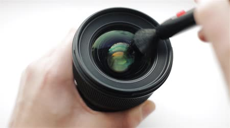 Hands of photographer or videographer cleans front glass of a lens from dust and dirt with the help of a professional cleaning pen. Modern camera Lens cleaning with brush.