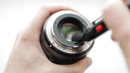 The photographers hands clean the back side of the modern lens at an angle with the help of a professional optics cleaning system. Brush for care of phototechnics.