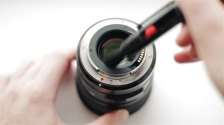 The photographers hands clean the back side of the modern lens from dust with a professional pencil to care for the optics. Stock mozgókép