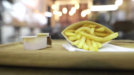 Hands of a hungry person is picking fast food french fries and dipping them in sweet and sour sauce. Visitors to cafes and lot of edison lamps on a blurred background. Evening time. Stock Footage