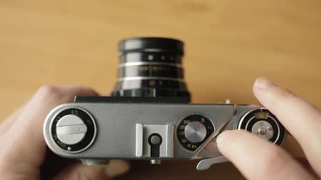 The photographer rewinds the film of the old film camera and presses the button.