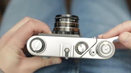 A young photographer changes settings of a vintage Soviet film camera, focuses and takes a picture. Close-up.