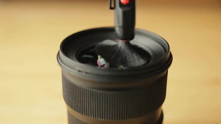 The photographer or videographer cleans front lens from dust and dirt with the help of a professional cleaning brush.