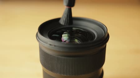 macro fotografia : Hands of photographer or videographer cleans front glass of a lens from dust and dirt with the help of a professional cleaning pen. Modern camera Lens cleaning with brush.