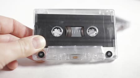 casette : Old vintage audio cassette on a white background in males hand.