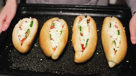 hardal : Homemade hot dogs on a baking sheet in the hands of a young girl. Housewife and fast food.