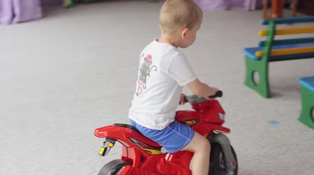 orphans : SUMY, UKRAINE - JUN 24, 2017: Children, orphans ride on toy motorcycles. Stock Footage