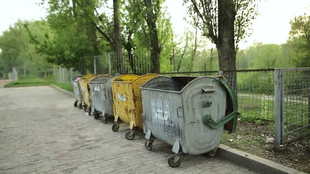 discard : SUMY, UKRAINE - MAY 04, 2018: Garbage bins with trash before the fence on the street in the city. Stock Footage