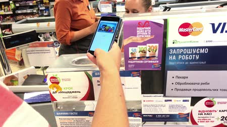 SUMY, UKRAINE - AUG 13, 2018: Customer paying with apple pay by mobile phone on terminal. Stock mozgókép