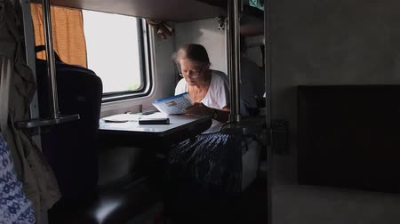 ODESSA, UKRAINE - SEP 10, 2018: Senior woman reading newspaper on the train.