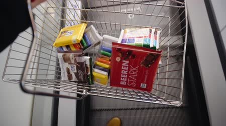 BERLIN, GERMANY - NOV 23, 2018: Ritter Sport chocolate with different filling. Grocery basket in the buyers hand, 4k.