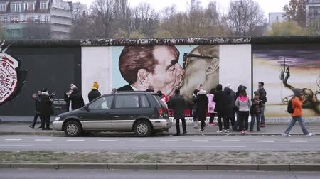bölmek : BERLIN, GERMANY - NOV 22, 2018: Tourists takes photos with the famous kiss from the Berlin Wall. 4k.