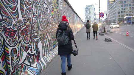 cold war : BERLIN, GERMANY - NOV 22, 2018: Woman with a camera walks near Berlin Wall. Slow motion. Stock Footage