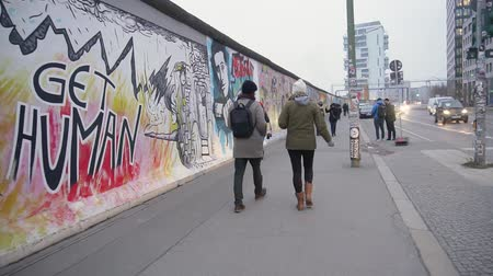 BERLIN, GERMANY - NOV 22, 2018: Young couple walks near Berlin Wall. Slow motion. Stock Footage