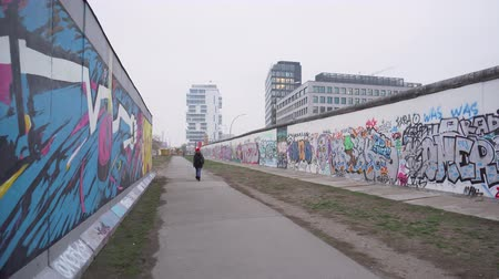 segmento : BERLIN, GERMANY - NOV 22, 2018: Girl in red hat walks near remains of the Berlin Wall.