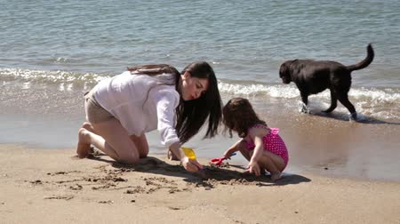 küçük kız : Young Hispanic mother and her little daughter drawing in the sand on a sunny day Stok Video