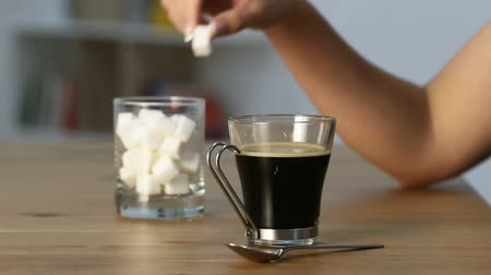 glikoz : Close up of a woman hand throwing sugar cube into a coffee mug on a table at home